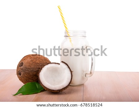 A huge mason jar with handle full of coconut milk and two tropical coconuts with leaf on a light wooden table, isolated on a white background. Whole and cut hawaiian coconuts. Fresh coconut milk.