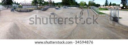 A huge panoramic image of an empty cement skate park - stock photo