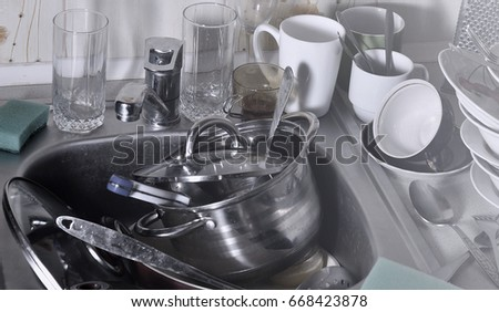 a huge pile of unwashed dishes in the kitchen sink and on the countertop a - Kitchen Sink Appliances