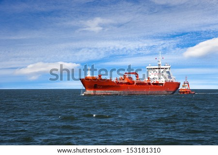 A huge red oil tanker and a tugboat at work. - stock photo