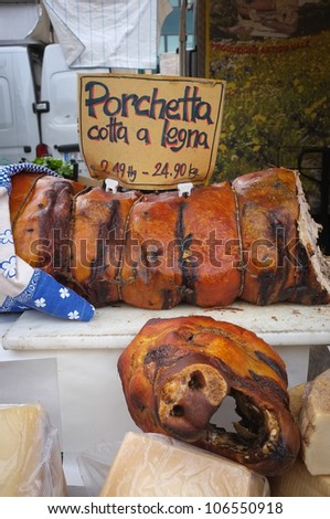 A huge slab of an Italian specialty food called Porchetta - stock photo