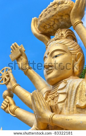 A huge statue of a multi armed buddha sits on a hill near to the city of Hua Hin in Thailand. - stock photo