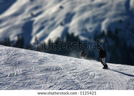 A human figure snowboarding in the Swiss alps. Scale difference between massive mountains and humans become apparent. - stock photo