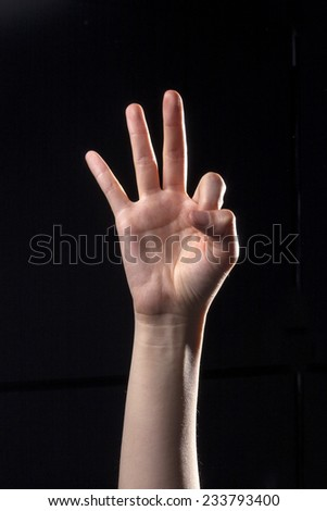 A human hand(finger) make the ok and means three in the china, san, chinese hand language isolated black at the studio.  - stock photo