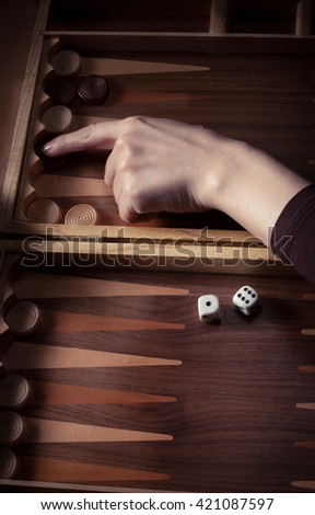 a human hand over the board Backgammon