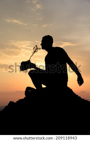 A human silhouette at sunset holding a plant with a piece of earth.