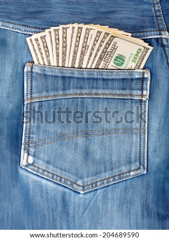 A hundred dollar bills sticking in the back pocket of denim blue jeans  - stock photo
