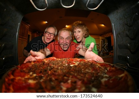 A hungry and excited family pull a Fresh Baked Pizza out of their oven for dinner. Pizza night.  Shot from the Inside of the oven facing out showing a unique view not often seen.  - stock photo
