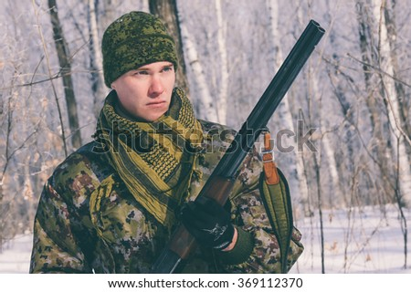 A hunter with a gun standing directly in Russian forest - stock photo