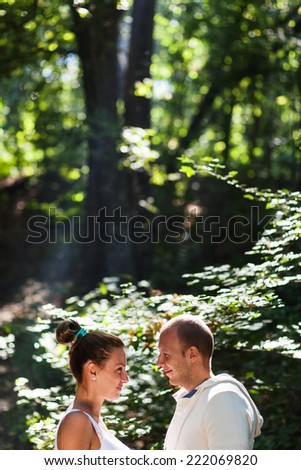 A husband and his pregnant wife looking at each other - stock photo