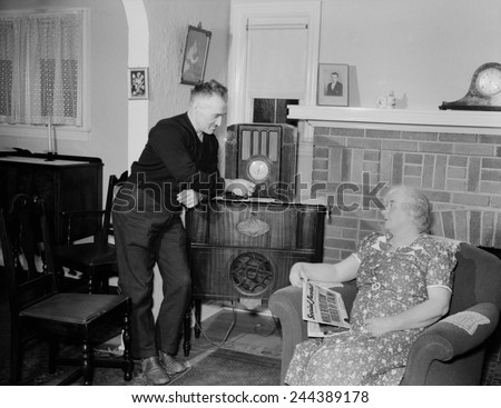 A husband tunes the radio while his wife holds populist right-wing radio priest, Father Coughlin's newspaper SOCIAL JUSTICE, with a headline, STALIN ORDERS WORLD REVOLUTION. 1938. - stock photo