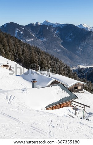 A idyllic mountain hut in front of winterly mountain range.