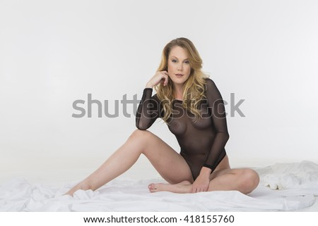 A implied nude figure model posing in a studio environment - stock photo