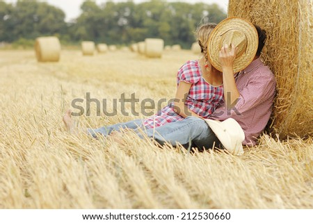 a in love young couple on haystacks in cowboy hats - stock photo