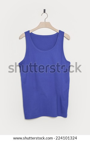 A indigo sleeveless shirt front side with wooden hanger isolated white. - stock photo