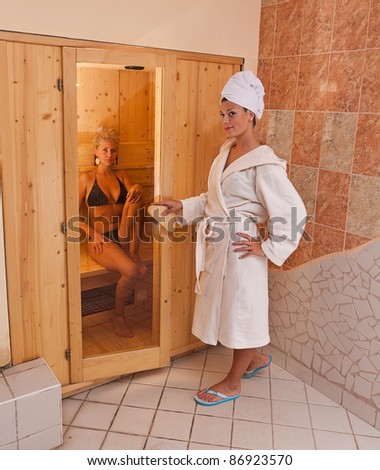 A infrared sauna cabin with two sexy womans - stock photo
