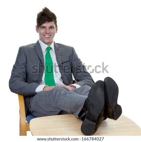 A isolated image of a businessman resting and relaxing with his feet resting up on the desk.