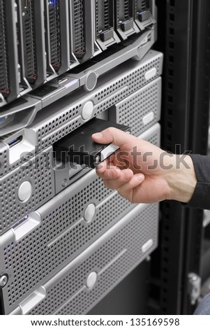 A IT engineer / technician / consultant insert a backup tape in a backup robot in a rack. Shot in a data center with blade servers and disk enclosures.