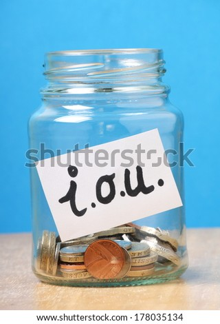 A jam jar part filled with british coins for savings has been slapped with a white sticker that says I.O.U. the abbreviation for I Owe You
