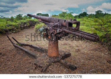 A Japanese anti-aircraft gun, left over from World War II, slowly rusts in a field on the island of Yap, Micronesia. - stock photo