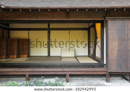 A japanese home made of wood, with the walls open into the garden.