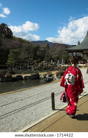 A Japanese woman in traditional dress at a temple in Kyoto. - stock photo