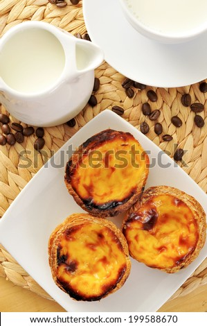 a jar and a cup with milk, and some pasteis de nata typical Portuguese egg tart pastries, on a set table - stock photo