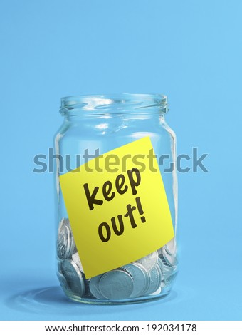 A jar of coins, with keep out reminder note inside the jar.  - stock photo