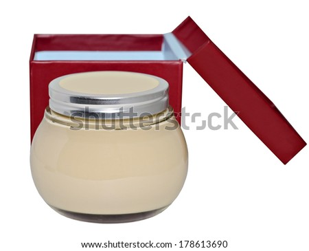 A jar of lotion or cream on a white background with a red and blue box. - stock photo