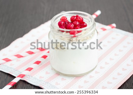 A jar of  plain yogurt with oats and red currant on a wooden table with striped straws and heart-shaped napkin. Healthy breakfast choice. - stock photo