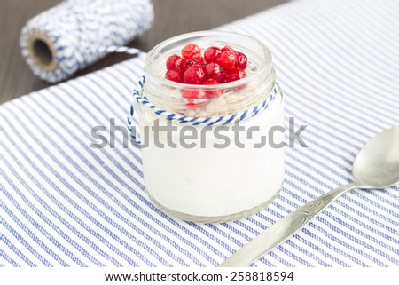A jar of  plain yogurt with oats and red currant on a wooden table with striped table cloth. Healthy breakfast choice. - stock photo