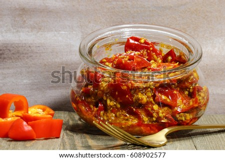 A jar of red chili pickle marinated in mustard seeds, and mustard oil and Indian pickling spices