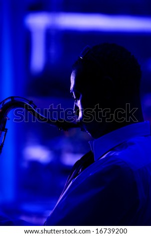 a jazz musician plays his saxaphone, in these moody images - stock photo
