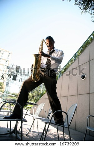a jazz musician stands on two chairs while playing his sax during an outdoor concert
