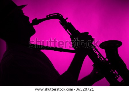 A jazz saxophone being played in silhouette against a low key pink background in the horizontal format. - stock photo