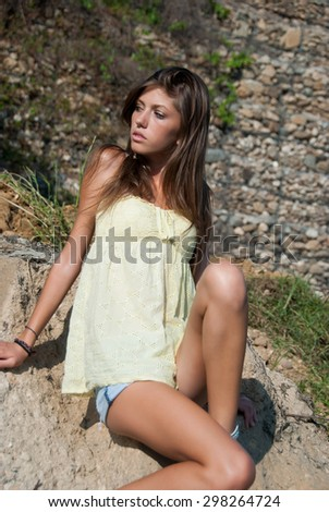 A jean short and yellow shirt for a young slim lady. She is sitting down and look away of the camera enjoying the view