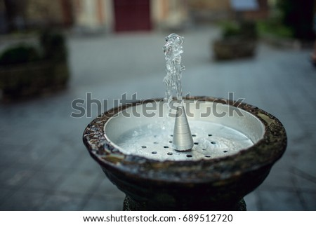 a jet of water in traditional drinking water fountain water drops at a old fountain