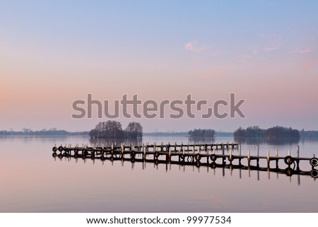 A jetty reflected in the still water of a Dutch lake at sunset - stock photo