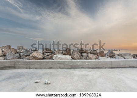 A jetty with some rocks mounted as a breakwater, during sunset hour, located in a Greek island. - stock photo