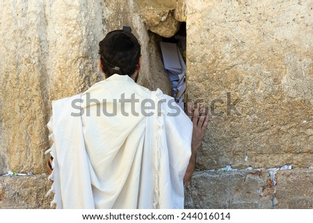 A jewish man is praying against the western wall in the old city of Jerusalem - stock photo