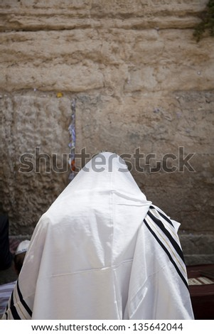 A Jewish man wearing a Jewish praying Shawl standing and parying infront of the wailing wall in the old city of Jerusalem. - stock photo