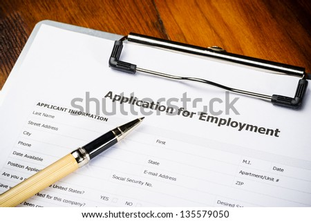 a job application on a clipboard with a gold pen
