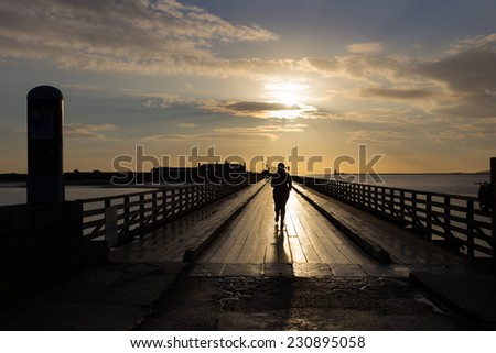 A jogger crossing Bull Bridge at Dollymount in the early morning - stock photo