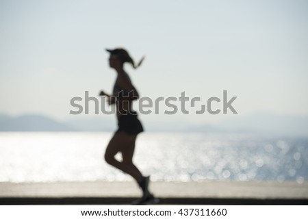 A jogger passes in abstract defocus blur silhouette on the Copacabana boardwalk in Rio de Janeiro, Brazil - stock photo