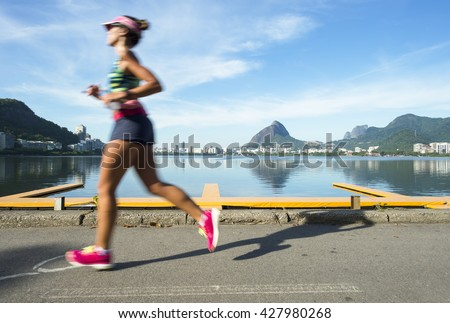 A jogger running past in motion blur a calm morning view of Lagao Rodrigo de Freitas lagoon, a popular recreation destination in Rio de Janeiro, Brazil - stock photo