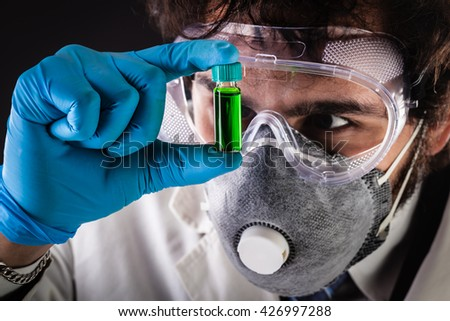 a joung and handsome doctor or researcher with a white lab coat holding a vial with green fluid - stock photo