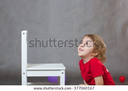 A joyful boy of three years old is looking up as if there was something interesting. Gray background