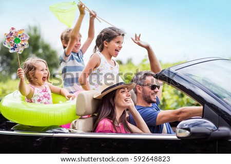 A joyful family, in a convertible car, goes on holiday to the sea. Children have colorful buoys and landing nets. Focus on the mother