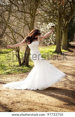 A joyous bride on a wooded path outside.