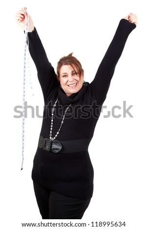 A jubilant woman raises her arms in triumph at achieving her goal. - stock photo